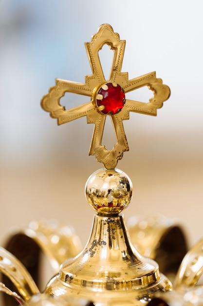 Couronnes de mariage dorées avec des pierres précieuses posées sur la table dans l'église Photo Premium
