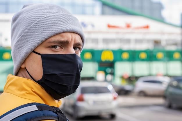Courrier Alimentaire Avec Masque Médical Noir Sur Le Parking. Service De Livraison De Nourriture Photo gratuit