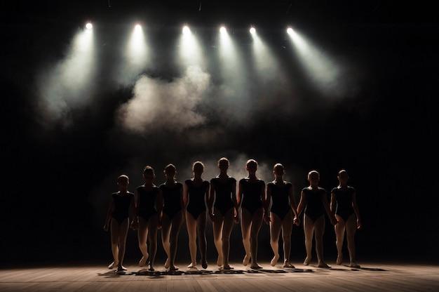 Cours de ballet sur la scène du théâtre avec lumière et fumée. les enfants sont engagés dans des exercices classiques sur scène. Photo Premium