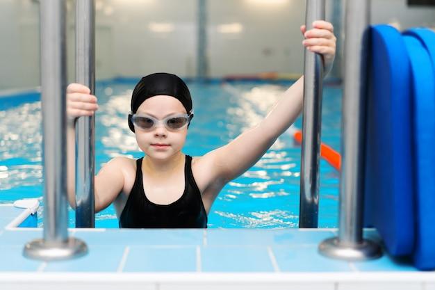 Cours de natation pour les enfants dans la piscine - belle fille à la peau claire nage dans l'eau Photo Premium