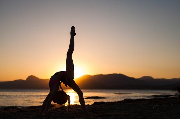 Cours De Yoga Au Coucher Du Soleil. Photo Premium