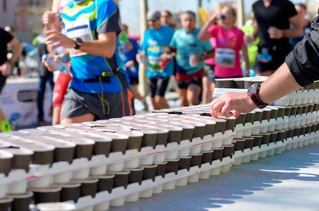 Course de marathon, coureurs sur la route, bénévole donnant de l'eau et des boissons isotoniques au rafraîchissement Photo Premium
