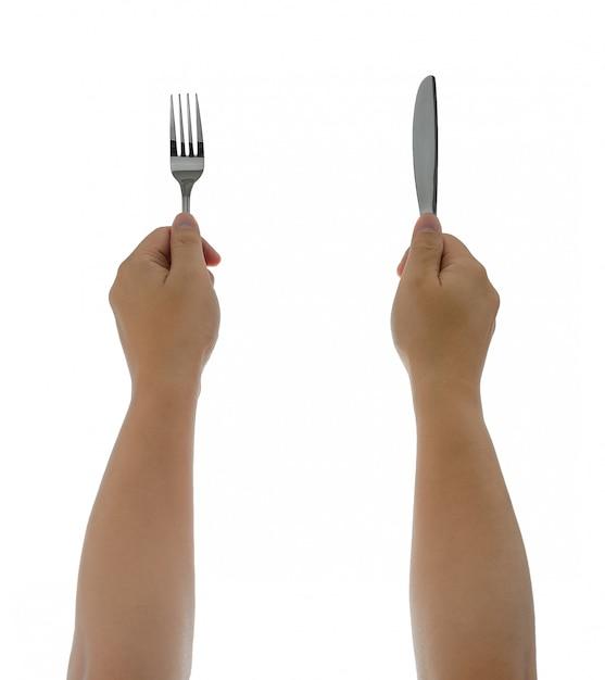 Un couteau et une fourchette tenus par les mains de l'homme. isolé Photo Premium