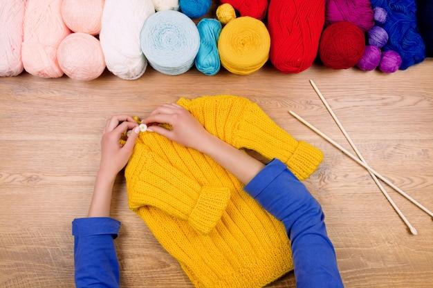 Couturier en milieu de travail. femme, mains, confection, bottes jaunes, bébé, pull jaune, à, pelote jaune Photo Premium