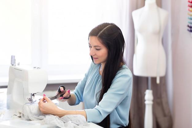 Couturière souriante se bouchent dans l'atelier, concept de petite entreprise avec fond de lumière du soleil Photo Premium