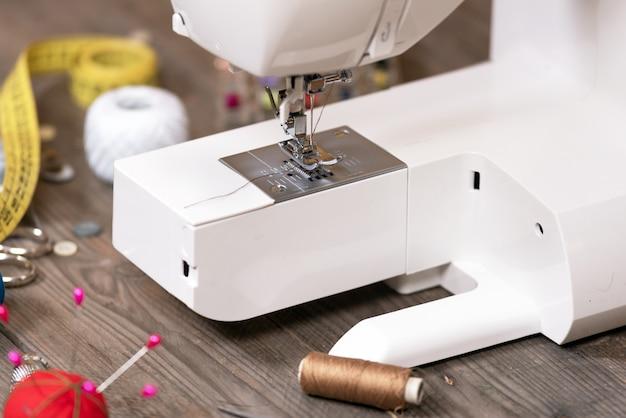 Couturière ou tailleur de fond avec des outils de couture, des fils colorés, une machine à coudre et des accessoires. Photo Premium