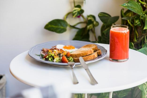 Couverts avec assiette grise de petit-déjeuner et smoothies sur une table blanche ronde Photo gratuit