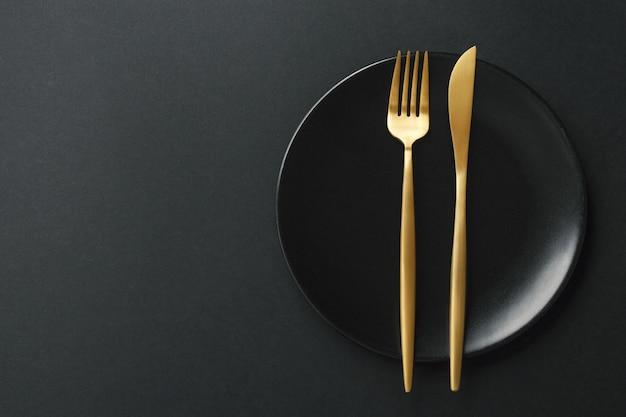 Couverts en or sur fond noir Photo gratuit
