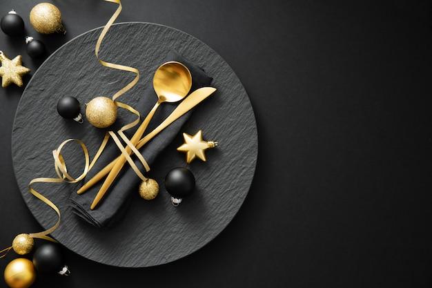 Couverts en or servis sur une assiette pour le dîner de noël Photo Premium