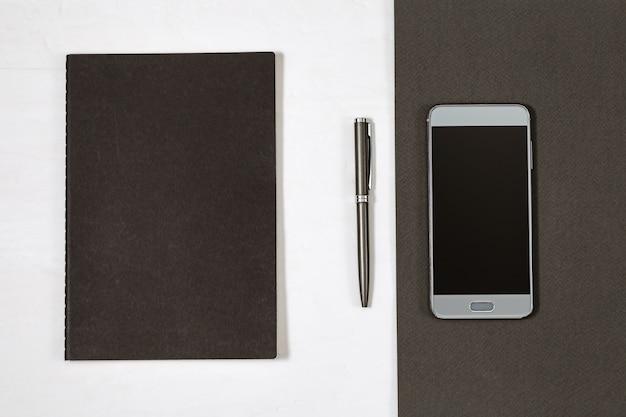 Couverture noire du cahier fermé et du stylo argenté. vue de dessus Photo Premium