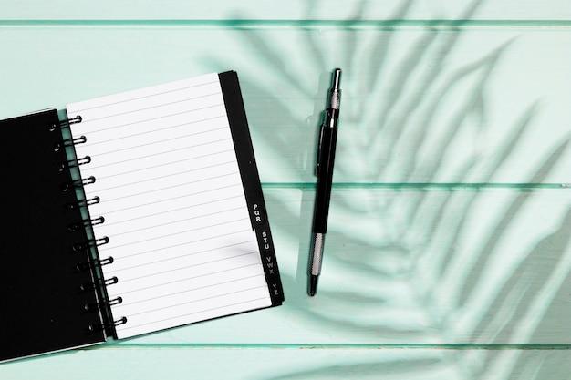 Couverture noire du cahier avec un stylo et des feuilles d'ombre Photo gratuit