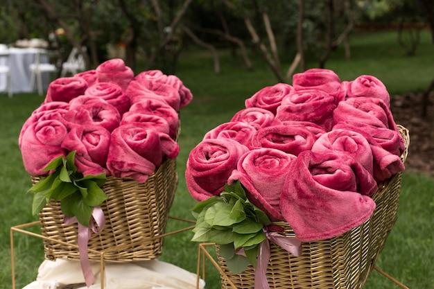 Des couvertures roses chaudes enroulées sous la forme de roses dans un grand panier pour les invités lors d'une fête de mariage en plein air Photo Premium