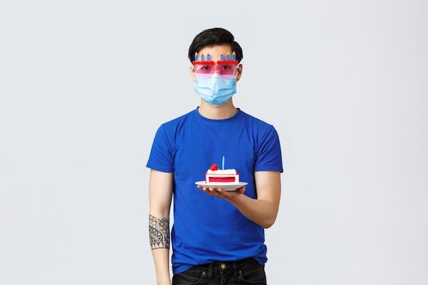Covid-19 Et Concept De Style De Vie. Jeune Homme Asiatique Réticent Dans Des Verres Drôles Tenant Un Gâteau D'anniversaire Sans émotions, La Haine Célèbre La Maison Pendant La Pandémie Photo Premium