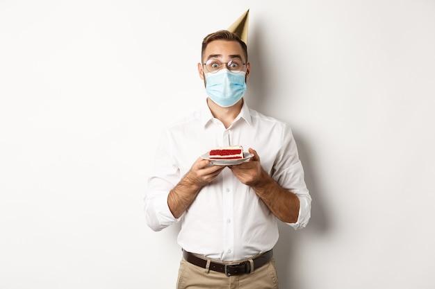 Covid-19, Distanciation Sociale Et Célébration. Gars D'anniversaire Surpris Tenant Un Gâteau Bday, Portant Un Masque De Coronavirus, Fond Blanc. Photo Premium