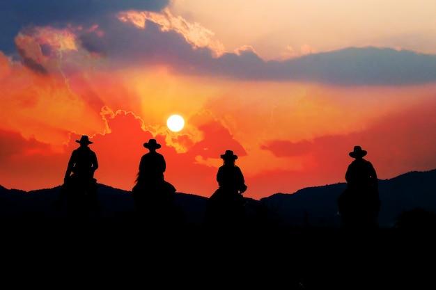Cowboy à cheval avec vue sur les montagnes et le ciel coucher de soleil. Photo Premium