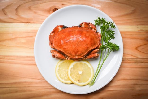 Crabe cuit sur une assiette blanche avec des herbes et des épices au citron Photo Premium