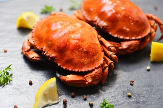 Crabe cuit sur une assiette noire avec des herbes et des épices au citron Photo Premium