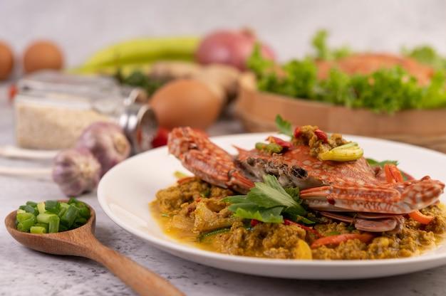 Crabe Sauté De Curry En Poudre Sur Une Plaque Blanche Sur Le Sol En Ciment. Photo gratuit
