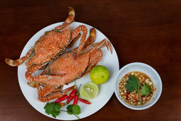 Crabes bleus avec trempette dans une assiette, sur un fond en bois, vue de dessus Photo Premium