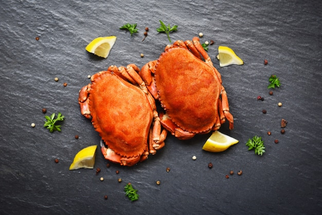 Crabes cuits au citron sur une assiette servie dans une assiette noire - fruits de mer cuits à la vapeur de crabe Photo Premium