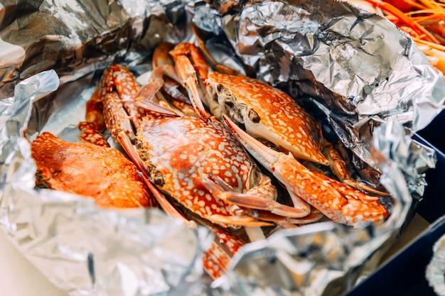Crabes à la vapeur thaïlandais à la vapeur dans la coquille qui enveloppent avec du papier d'aluminium. Photo Premium