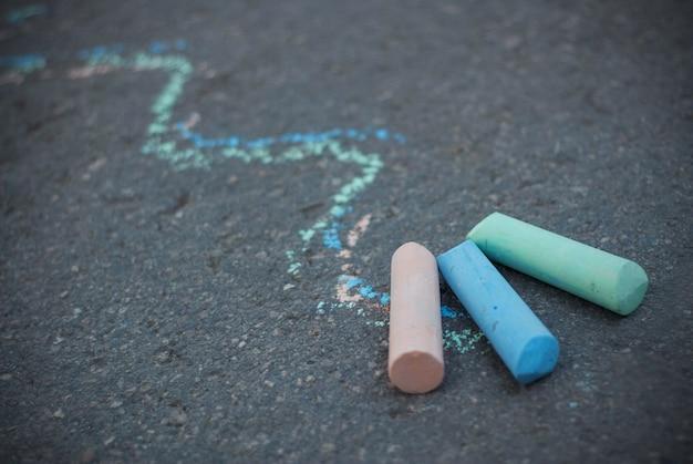 Craie sur l'asphalte texturé. lignes de dessin colorées. enfance et parentalité. éducation. Photo Premium