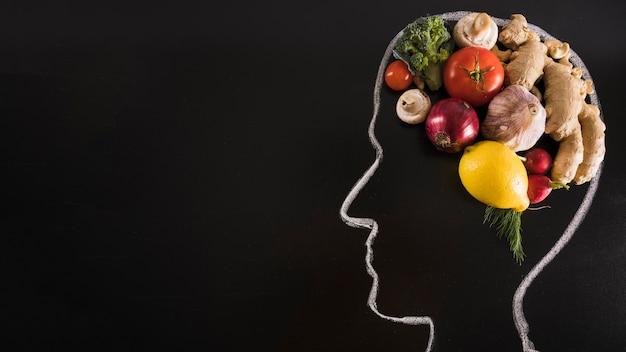 Craie dessinée tête humaine avec de la nourriture saine pour le cerveau sur tableau noir Photo gratuit