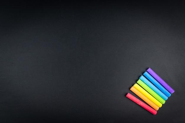 Craie multicolore sur fond de tableau noir Photo Premium