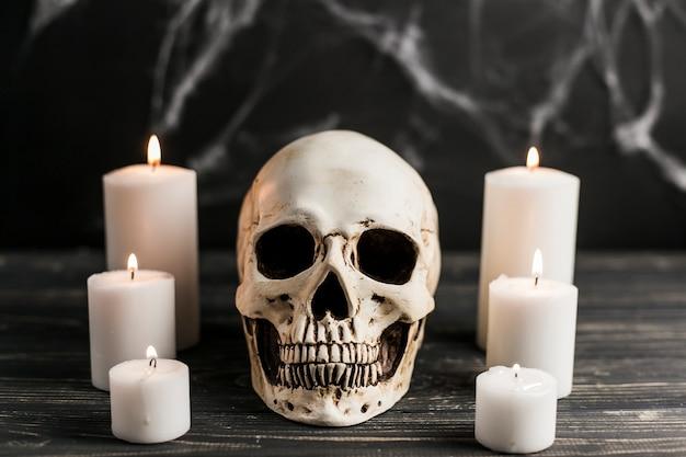 Crâne blanc et bougies allumées Photo gratuit