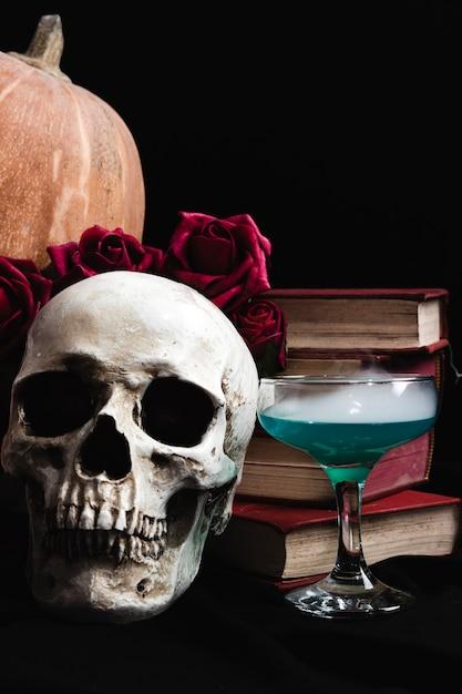 Crâne avec une boisson verte, des livres et des roses Photo gratuit