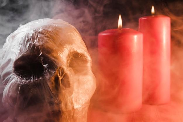 Crâne dans un sac en plastique et des bougies en fumée Photo gratuit