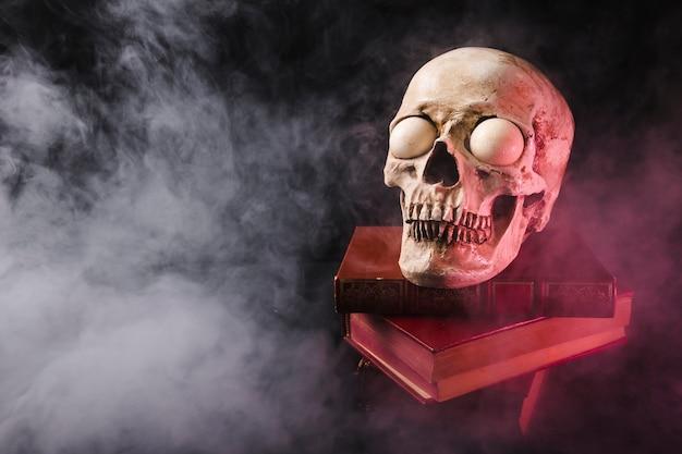 Crâne effrayant sur des livres empilés dans la fumée Photo gratuit