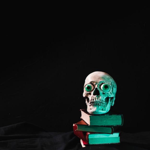 Crâne effrayant avec des yeux de fantaisie se trouvant sur une pile de livres Photo gratuit