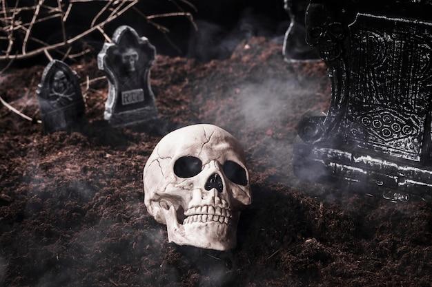 Crâne humain en fumée au cimetière d'halloween Photo gratuit