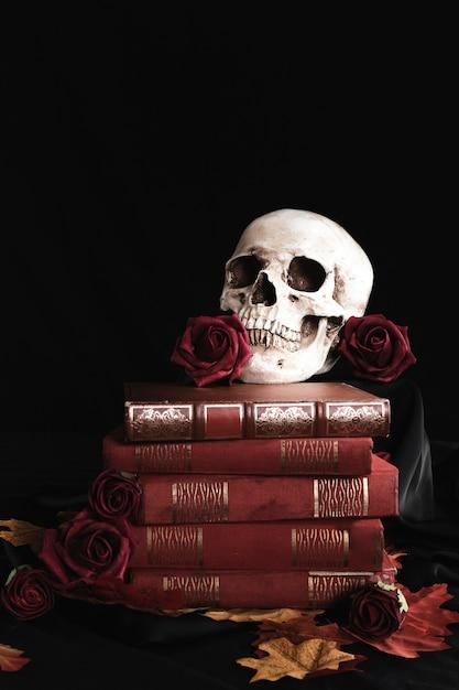 Crâne humain avec des roses sur les livres Photo gratuit