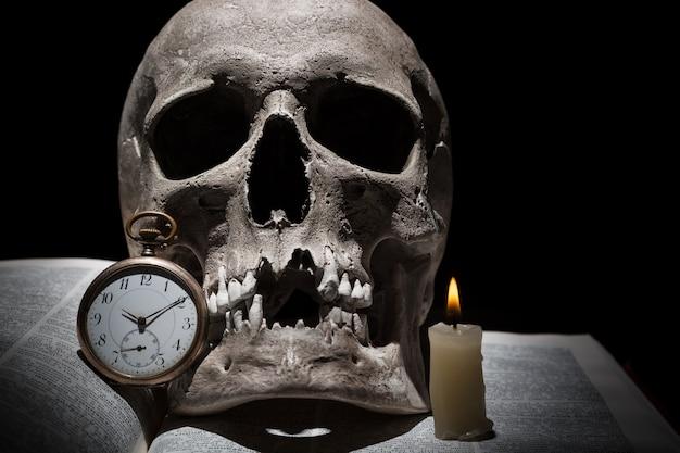 Crâne humain sur vieux livre ouvert avec bougie allumée et horloge vintage sur fond noir sous faisceau de lumière se bouchent Photo Premium