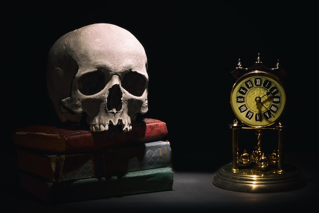 Crâne humain sur les vieux livres près de rétro horloge vintage sur fond noir sous le faisceau de lumière. Photo Premium