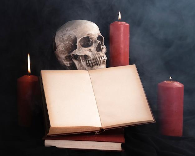 Crâne avec maquette de livre et bougies Photo gratuit