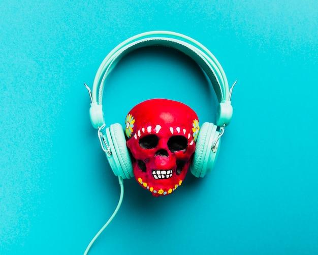 Crâne plat rouge avec des écouteurs Photo gratuit