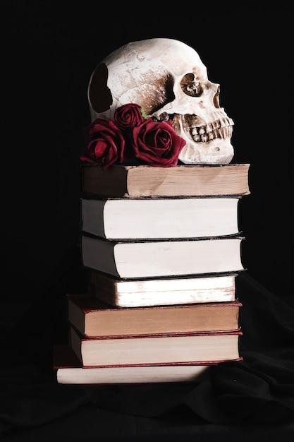 Crâne avec des roses sur des livres Photo gratuit