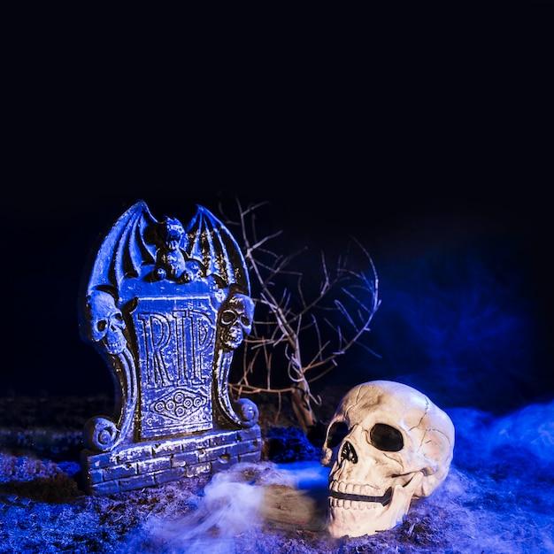 Crâne sombre près de la pierre tombale au sol Photo gratuit