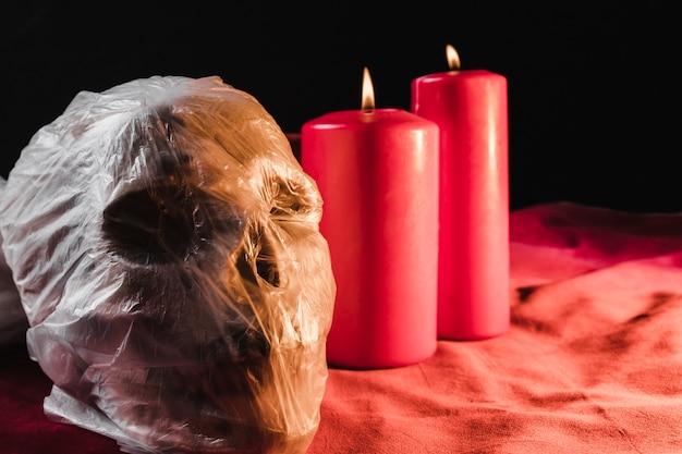 Cranium emballé dans un sac en plastique et des bougies allumées Photo gratuit