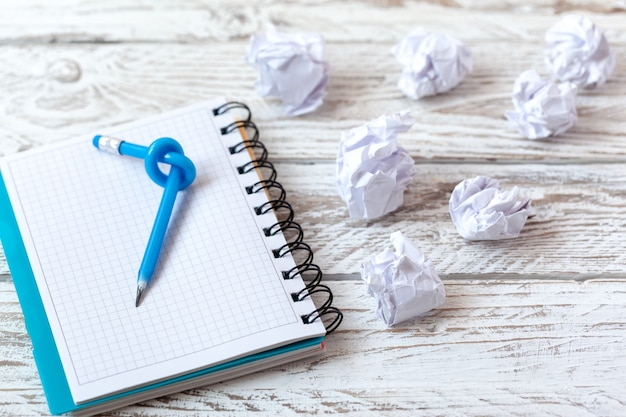 Crayon bleu avec noeud sur un pavé d'écriture sur bois blanc. Photo Premium