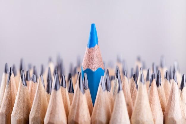 Un crayon bleu taillé parmi beaucoup d'autres Photo Premium