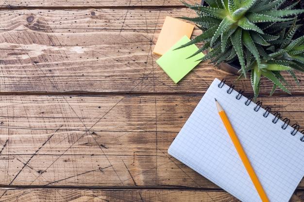 Crayon et bloc-notes avec spirale sur une table en bois texturée. concept de bureau et d'école. mise au point sélective. espace de copie. Photo Premium