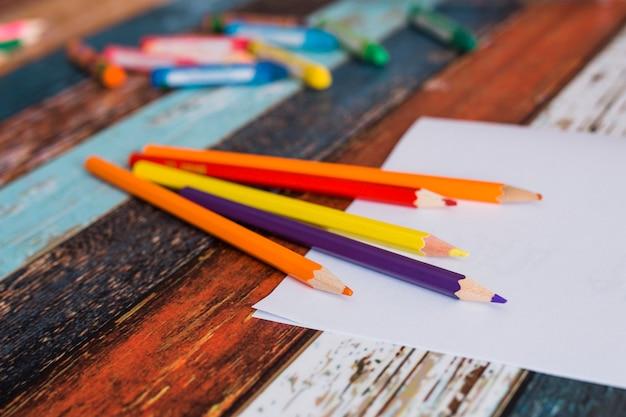 Crayon coloré, couleur et papier blanc sur une vieille table peinte Photo gratuit