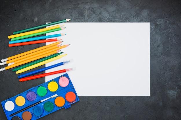Crayon coloré; stylo feutre; palette d'aquarelle avec du papier blanc vierge Photo gratuit