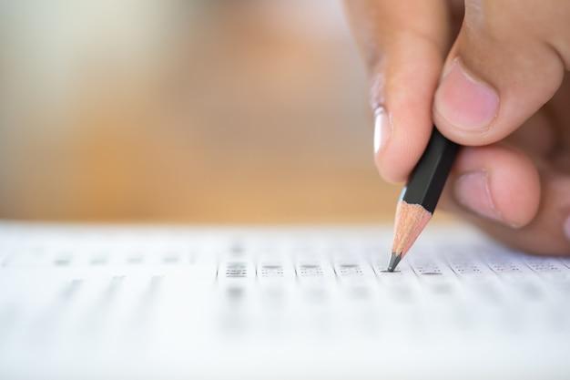 Crayon sur la main qui écrit la réponse de l'examen de la question Photo Premium