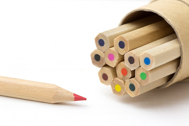 Crayon rouge se démarquant de la foule sur la table blanche. Photo Premium