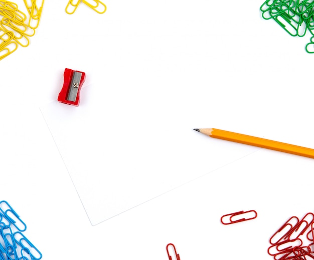Crayon, taille-crayon, trombones se trouvent sous différents angles de la feuille sur un fond blanc. image de héros et espace de copie. Photo Premium